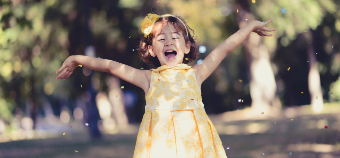 little girl playing with confetti in a park