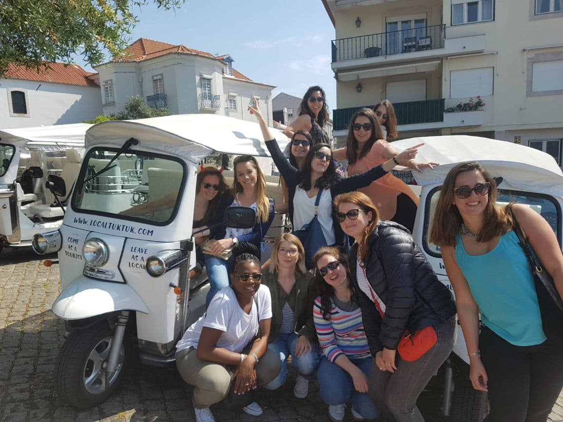 A group of smiling girls standing next to a white tuk tuk