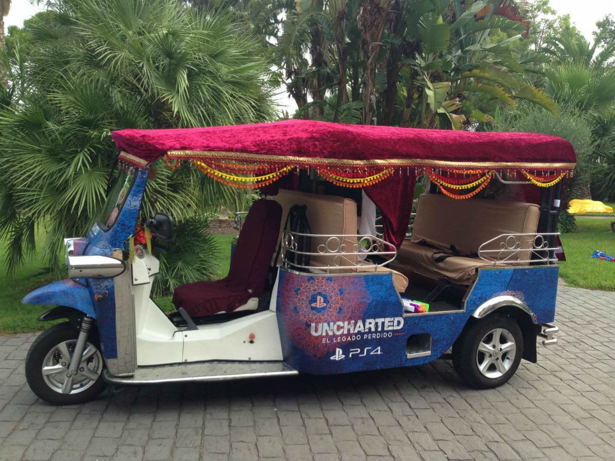 Side view of a tuk tuk decorated for the official release of Uncharted: The Lost Legacy game