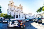 Several vehicles, including a tuk tuk, parked in front of Sao Vicente de Fora Monastery in Lisbon