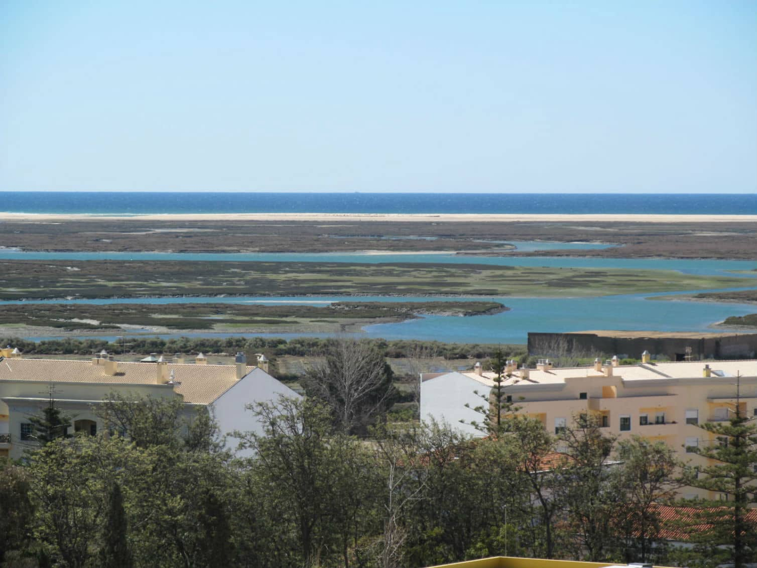 Two apartment buildings facing the salt marshes and ocean at the Ria Formosa Natural Park in Faro