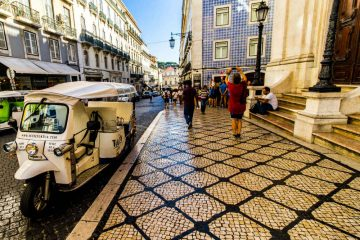 A tuk tuk from Local Tuk Tuk parked next to the sidewalk in Chiado (Lisbon)