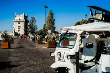 Side of a white tuk tuk with the belem tower in the background