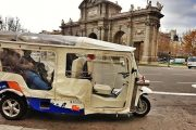 Tuk tuk parked with people inside and with the Puerta de Alcalá has the background