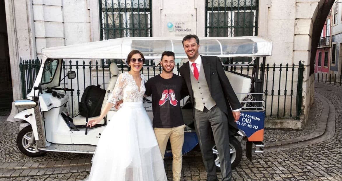 Bride and groom laughing with their driver with a tuk tuk as the background